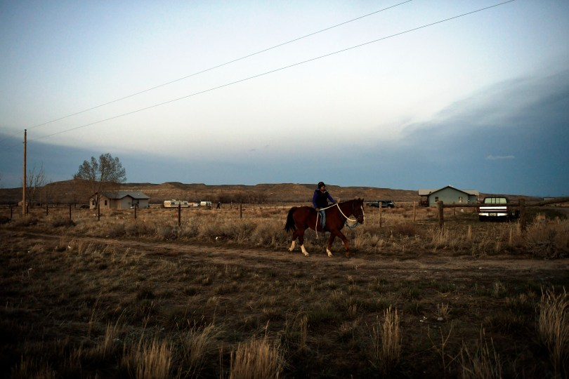 Autumn Behan, 26, riding her uncles hunting horse Savage home bareback in the late evening after he slipped away from the pasture about 8 miles outside Ethete, Wyo. on April 10, 2017.