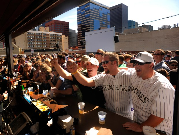 Rockies fans Chris Swedhin, left, Cody Huff, center, and Todd Kirkman, right, watch a Rockies game on a television behind the rooftop bar at The Tavern Downtown, 1949 Market Street.