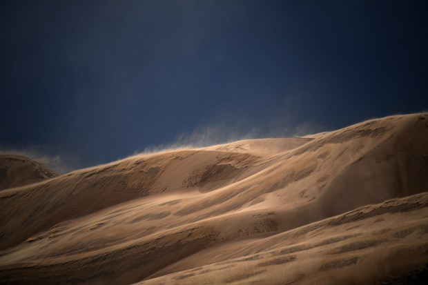 Strong winds and light rain blowing sand up and over the dunes at Great Sand Dunes National Park