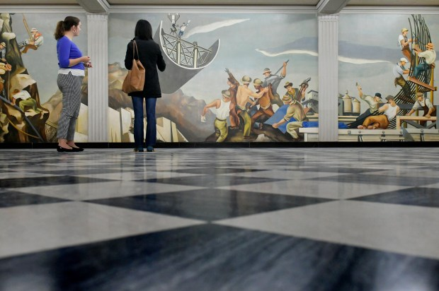 """The director of the Department of the Interior's museum, Diana Ziegler, left, shows the """"Creation of a Dam,"""" one of the largest murals in the building."""