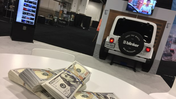 Wads of $100 bills are stacked on a table at the Blinker booth