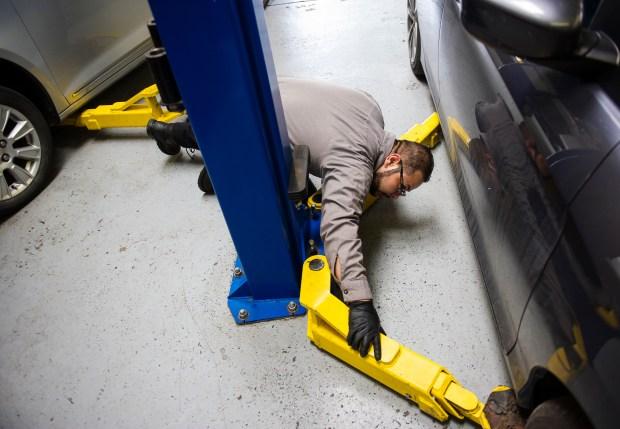 Head technician Nelson Garcia positions car ...