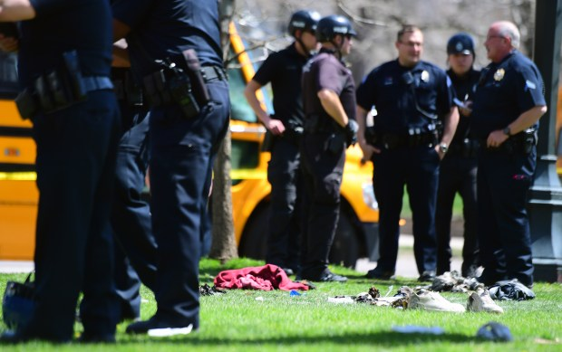 A pile of shoes and some belongings, along with some wilted grass, is left behind after a man lit himself on fire in Denver's Civic Center Park while in Denver Police Department handcuffs on Thursday, April 13, 2017.