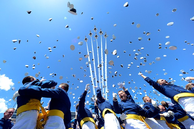 Cadets throw their hats in the air as the Air Force Thunderbirds fly over the U.S. Air Force Academy graduation ceremony on June 2, 2016, in Colorado Springs.