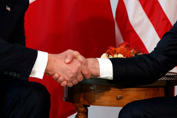 President Donald Trump (left) shakes hands with French President Emmanuel Macron during a meeting at the U.S. Embassy in Brussels on Thursday.