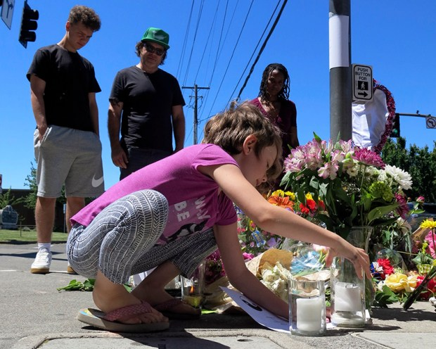Coco Douglas, 8, leaves a handmade sign and rocks she painted at a memorial in Portland, Ore., on Saturday for two bystanders who were stabbed to death Friday while trying to stop a man who was yelling anti-Muslim slurs and acting aggressively toward two young women.