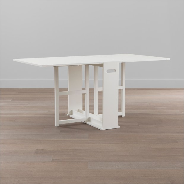 The Span gateleg dining table from Crate and Barrel can be tucked behind a sofa when not in use.