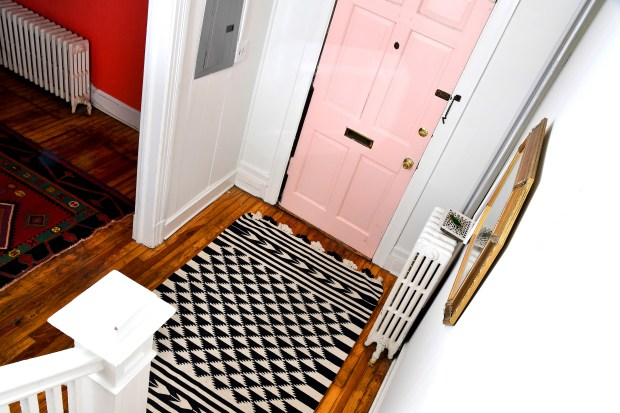 The author painted the foyer door millennial pink and added a gold-framed octagonal mirror and patterned rug. Foyer Total budget: $100.