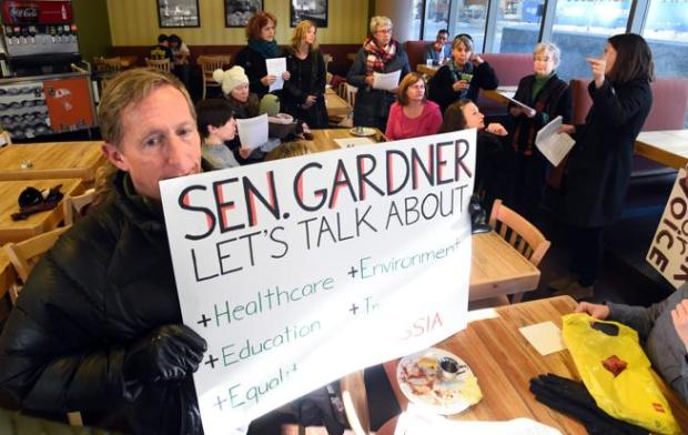 Gregg Olsen, left, brought a sign to the strategy meeting in January before a walk to the office of U.S. Sen. Cory Gardner, R-Colo. Groups such as Indivisible Front Range Resistance vow to hold Gardner accountable as the House's American Health Care Act begins to work its way through the Senate.
