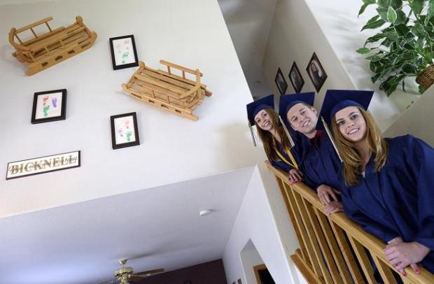 The Bicknell triplets, Nicole, left, Brandon, center, and Sonya, right, pose for a photo in their caps and gowns Friday before graduation from Colorado Early Colleges in Fort Collins. The triplets, who also just received their associate degrees, have overcome many challenges to get to this high school graduation day.