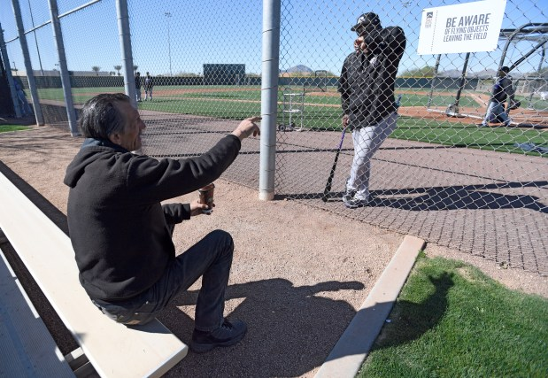 Colorado Rockies fan Angelo sits on the bleachers and chats with Rockies coach Stu Cole during practice at Salt River Fields at Talking Stick