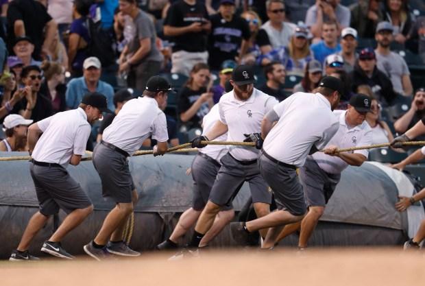 Grounds crew members pull the tarp ...