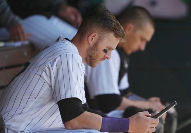 Colorado Rockies' Trevor Story studies a tablet before facing Washington Nationals relief pitcher Matt Albers during the seventh inning of a baseball game Thursday, April 27, 2017, in Denver. Washington won 16-5. (AP Photo/David Zalubowski)