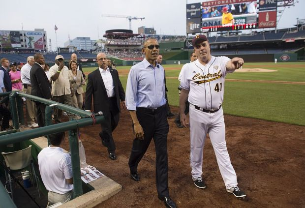 President Barack Obama walks alongside Representative Dan Kildee (R), Democrat of Michigan, during the annual Congressional Baseball Game between the Democrats and Republicans in Congress at Nationals Park in Washington, D.C., June 11, 2015.