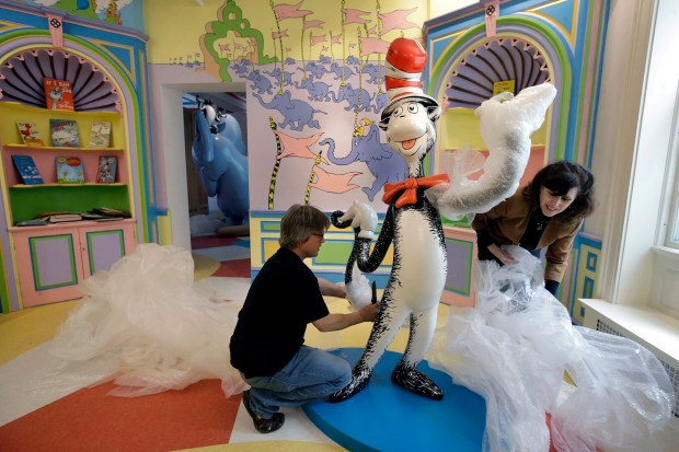 """John Simpson, left, project director of exhibitions for The Amazing World of Dr. Seuss Museum, and his wife Kay Simpson, right, president of Springfield Museums, unwrap a statue of the """"Cat in the Hat,"""" at the museum, in Springfield, Mass. The museum devoted to Dr. Seuss, which opened on June 3 in his hometown, features interactive exhibits, a collection of personal belongings and explains how the childhood experiences of the man, whose real name is Theodor Geisel, shaped his work."""