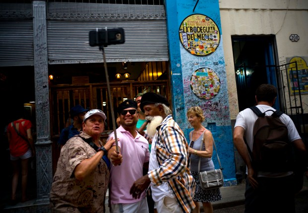 Tourists take a selfie at the Bodeguita Del Medio bar in Havana, Cuba. President Donald J. Trump's new policy on Cuba travel has winners and losers: Group tour operators hope to sell more trips, but bed-and-breakfast owners in Cuba said they're losing business.