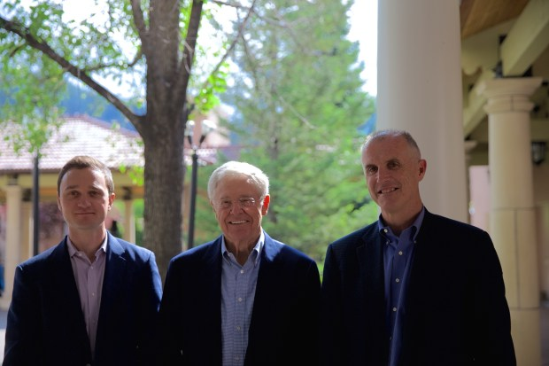Brian Hooks, Charles Koch Mark Holden in Colorado Springs on June 24, 2017.