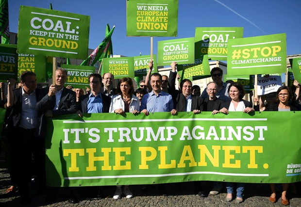 The top candidates of the Green Party for the Germany's parliamentary elections, Katrin Goering-Eckardt, center left, and Cem Ozdemir, center, protest against President Donald Trump's decision to exit the Paris climate agreement in front the the U.S. embassy in Berlin on Friday.