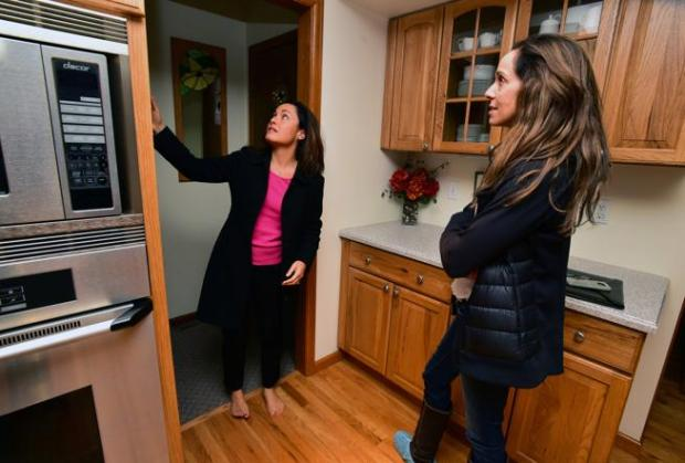Spaces Realtor Rebecca Holley, left, discusses the kitchen area in a home she was showing to Shira Souvignier and her husband Tom in Boulder on April 28, 2017.