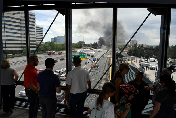 Pedestrians watch Wednesday's fuel tanker fire on Interstate 25 from RTD's Orchard Station bridge. Colorado Department of Transportation crews worked overnight to repair I-25 near the Denver Tech Center after a fuel tanker carrying diesel fuel crashed around noon Wednesday.