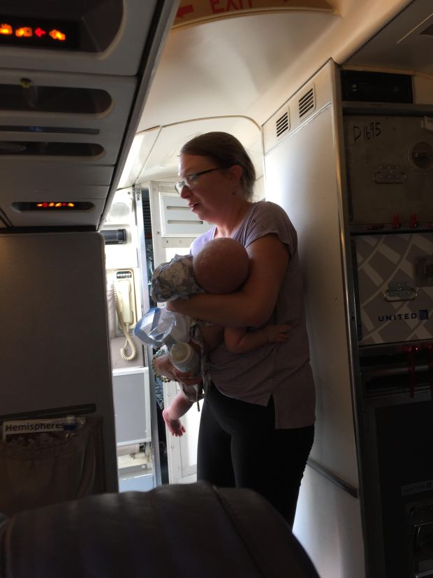 Emily France holds her four-month-old son, Owen, near an open door on United flight 4644 Thursday in Denver. France was waiting on an ambulance for her son who became overheated as the plane sat on the tarmac for nearly two hours. Owen was treated and released from Children's Hospital and is doing better, his mom said.