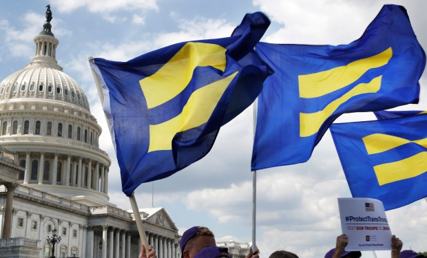 People with the Human Rights Campaign hold up flags during an event organized by Rep. Joe Kennedy, D-Mass., in support of transgender members of the military on Wednesday on Capitol Hill in Washington.