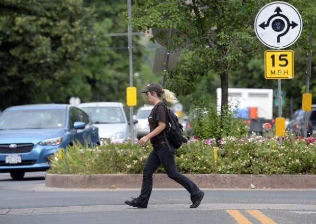 Amanda Rivera walks across the crosswalk in front of a roundabout at the intersection of 17th and Pine Streets on Monday while walking to work in Boulder. The City Council will consider giving money to projects, such as roundabouts, designed to decrease speeding in neighborhoods.