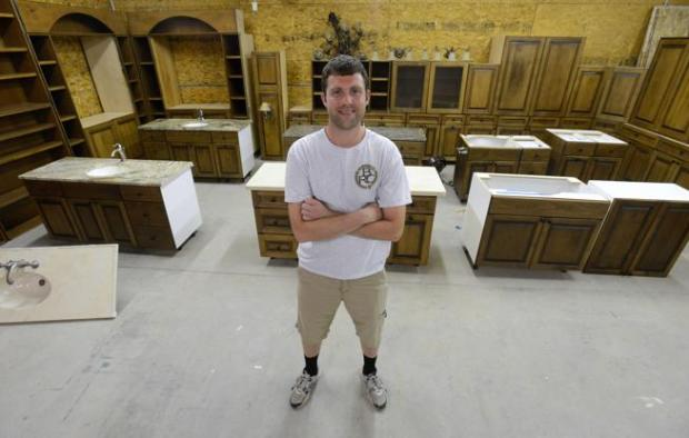 Ben Laning, owner of Ben's Repurposed Cabinetry, stands Monday amid the cabinets removed from a Fort Collins home and now available for sale in his Loveland warehouse. More than just kitchen cabinets, the walnut pieces came from the entire house and include library shelves, bathroom vanities and more.