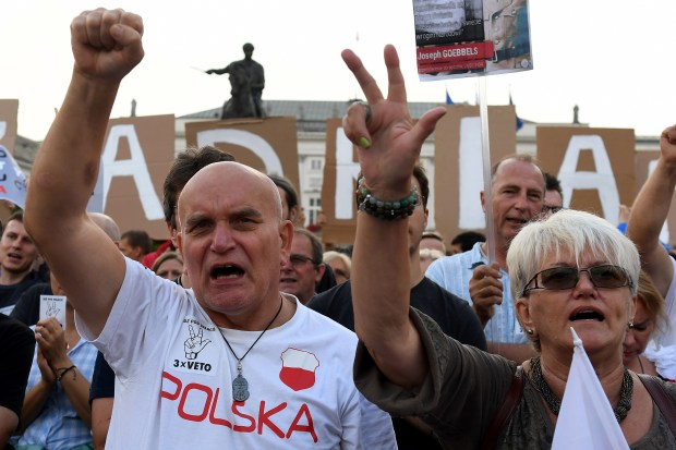 Protesters shout slogans during a protest on Sunday in front of the presidential palace in Warsaw.