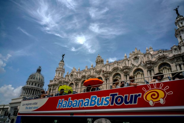 Tourists ride a tour bus ...