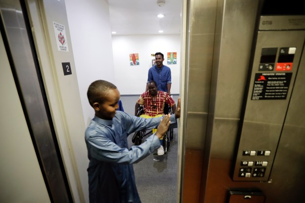 Ali Said, of Somalia, center, is pushed by refugee caseworker Mohamed Yassin, behind, as he makes his way into an elevator with his two sons Thursday, July 6, 2017.