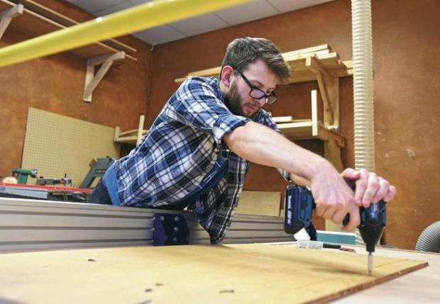 Jacob Dodd secures a piece of wood with a screw before cutting out a design with a Shop Bot machine at the Solid State Depot hackerspace in Boulder on Tuesday.