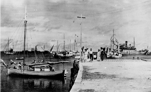 This undated photo discovered in the U.S. National Archives by Les Kinney shows people on a dock in Jaluit Atoll, Marshall Islands. A new documentary film proposes that this image shows aviator Amelia Earhart, seated third from right, gazing at what may be her crippled aircraft loaded on a barge.