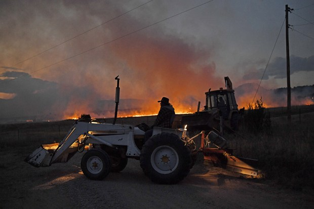Rancher Joe McWilliams watches from his tractor after he and neighbors dug fire lines to slow the progress of the Beulah Hill Fire on Oct. 3, 2016. The fire destroyed eight homes.