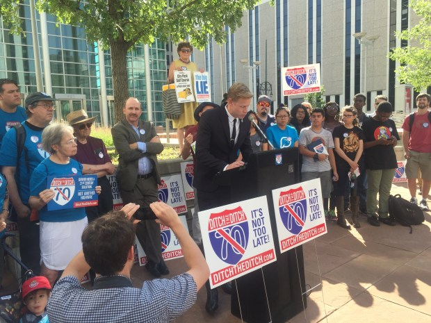 Opponents of the Interstate 70 expansion through northeast Denver flank developer Kyle Zeppelin outside the Alfred A. Arraj United States Courthouse downtown on July 10, 2017. He spoke during a news conference to announce a lawsuit challenging the project.