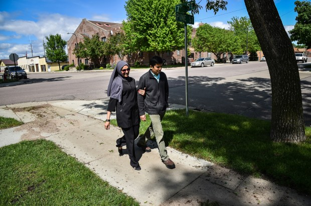 Dr. Ayaz Virji, 42, and his wife Musarrat Virji, 36, walks home from work on a May day in Dawson, Minn.