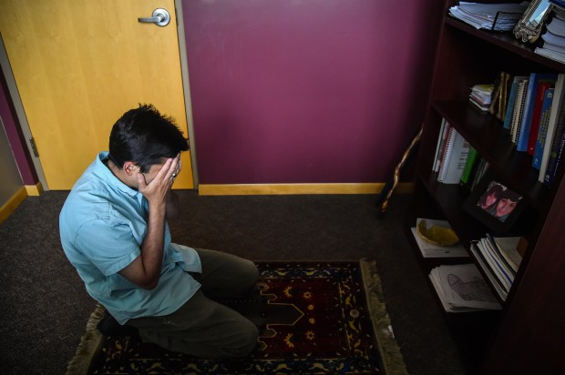 Dr. Ayaz Virji prays in his office after seeing a patient at the hospital where he works as a family medicine doctor, chief of staff and clinic medical director at Johnson Memorial Health Services in Dawson, Minn.