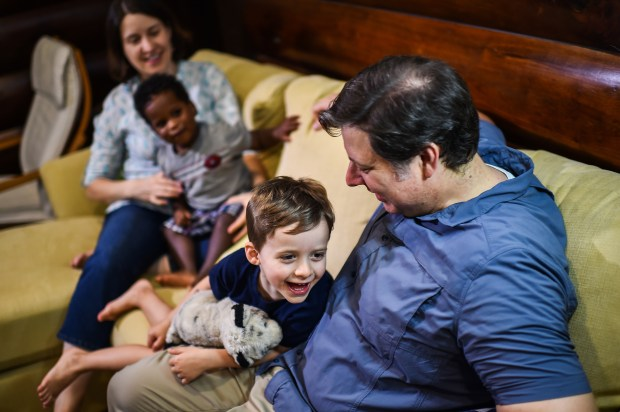 Episcopal priest James Isaacs, 40, with his wife, Maggie Brewinski Isaacs, 40, and their children, Jimmy Isaacs, 4, center, and Joseph Isaacs, 2, at home in Potomac, Md.