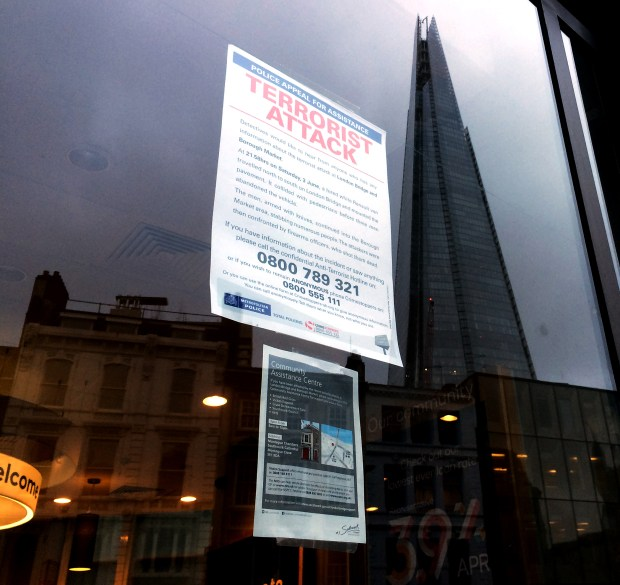 A sign posted in a storefront at Borough Market calls for information about the June attack. A reflection of the Shard, the tallest building in Western Europe, appears in the glass.