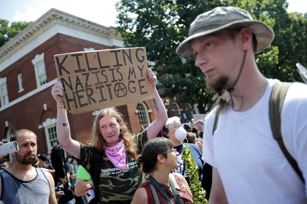 """Counter-protesters line the route taken by white nationalists, neo-Nazis and members of the """"alt-right"""" during the Aug. 12 """"Unite the Right"""" rally in Charlottesville, Va. After clashes between the two sides, the rally was declared an unlawful gathering and people were forced out of Lee Park, where a statue of Confederate General Robert E. Lee was slated to be removed."""