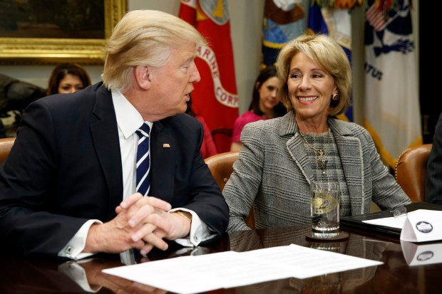 President Donald Trump and Education Secretary Betsy Devos speak during a Feb. 14 meeting with parents and teachers at the White House. The Trump administration supports the use of private-school vouchers.