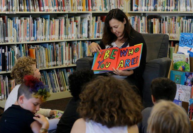 """In this Wednesday, July 12, 2017 photo, Sandra Collins, executive director and founder of enGender, reads a book to campers at the Bay Area Rainbow Day Camp in El Cerrito, Calif. Collins says, """"A lot of these kids have been bullied and had trauma at school. This is a world where none of that exists, and they're in the majority. That's a new experience for kids who are used to hiding and feeling small."""""""