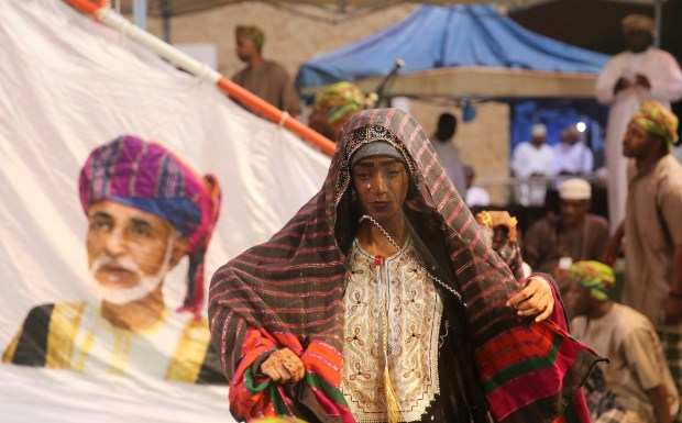 Members of a dance troupe, in traditional garb, wait to perform next to a giant sail adorned with a portrait of the Sultan of Oman, Qaboos al-Said, during a festival celebrating the monsoon season, in Salalah, southern Oman. The 60-day festival of dance competitions, concerts, exorcisms performed by Sufis and the moderate temperatures draws tens of thousands of tourists to the region each year.