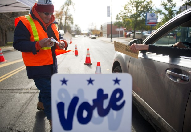 An election judge collects ballots from drive-up voters in front of the Denver Elections Division offices on Nov. 4, 2013.
