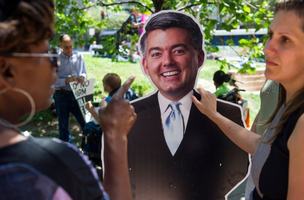 Atlantis ADAPT and Colorado Cross-Disability Coalition members and supporters speak in front of a cardboard cutout of Sen. Cory Gardner during a July 27 protest in Denver.