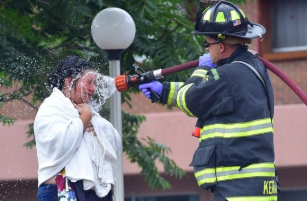 Firefighters spray a woman down during a possible hazmat situation at the Mesa Vista retirement home in Boulder on Wednesday.