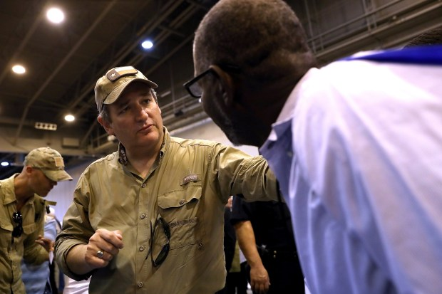 U.S. Sen. Ted Cruz, R-Texas, talks with a Hurricane Harvey evacuee while touring the NRG Center evacuation center on Monday in Houston.