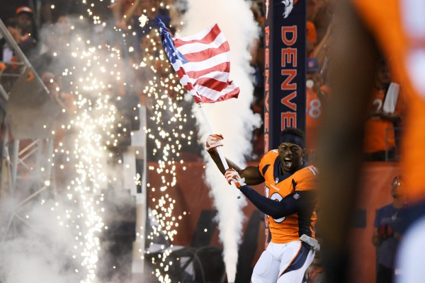 Wide receiver Emmanuel Sanders carries the American flag during a ceremony before the Broncos' game against the Los Angeles Chargers on Sept. 11. By seeking to divide the NFL's fans, owners and management from its players, President Donald Trump showed a frightening desire to divide the nation further.