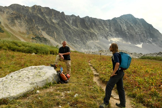 Hiker George Nick, left, talks with hiker Sean Cody, right, near Capitol Lake with the massive Capitol Peak behind them on Sept. 6, 2017 in the Maroon Bells-Snowmass Wilderness.