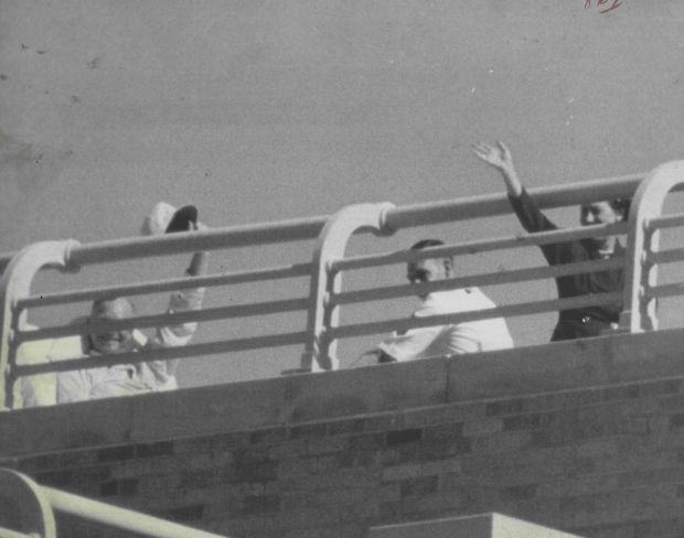 Sunbathing on Fitzsimons Army Hospital's 8th floor balcony, President Eisenhower gives a cheery wave for the first photo of the president since his heart attack on Oct. 13, 1955.